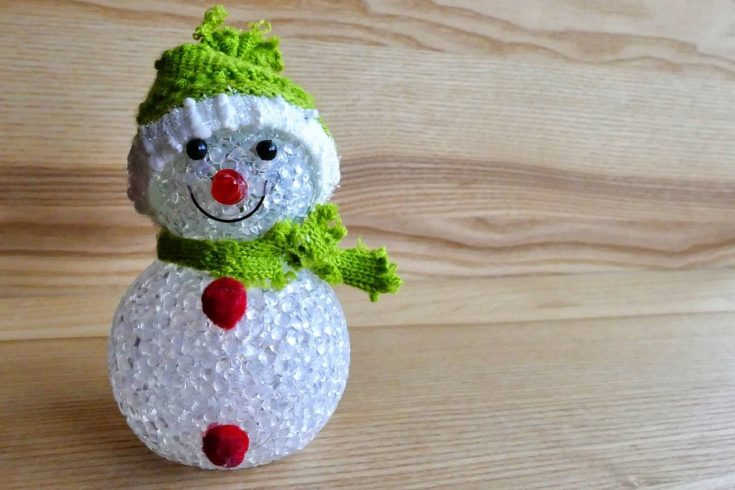 Crystal like body smiling snowman adorned with green cloth as hat and scarf with two red stuff on the body as buttons