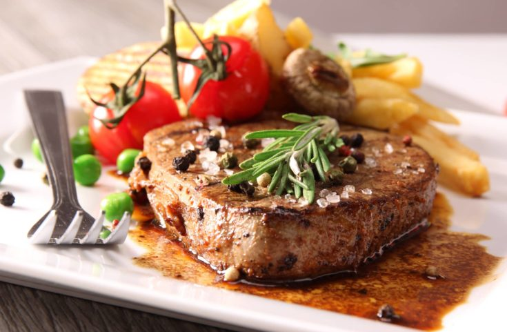 Grilled Beef Steak top with salt,pepper and herbs. Sauted with sauce,with a fork,tomatoe,beans,mushroom and fries,perfectly arrange in a white plate.