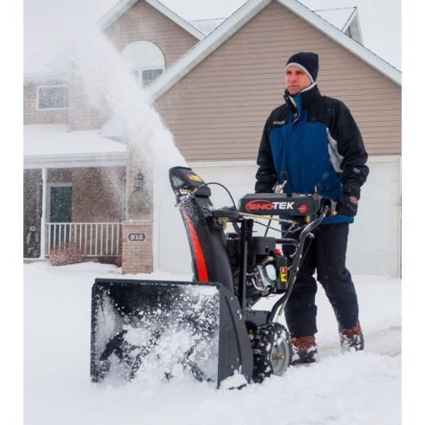 Man holding his Sno Tek Snow Blower driving it to clear snow on his yard.