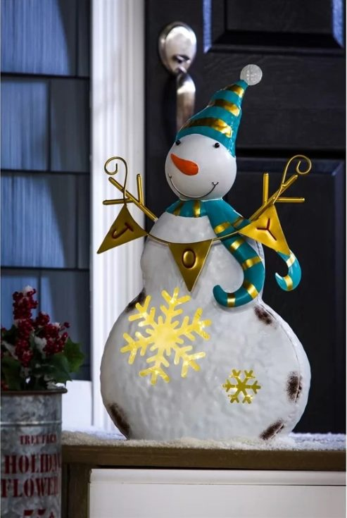 Snowman adorned with gold and blue green decorations holding a bunting with the word JOY in it placed outside