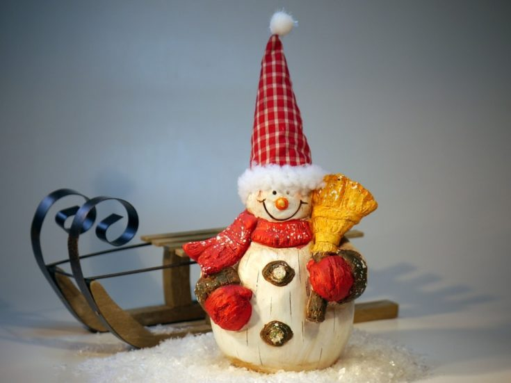 Carved from wood snowman holding a broom with a pointy hat and a sleigh on its background
