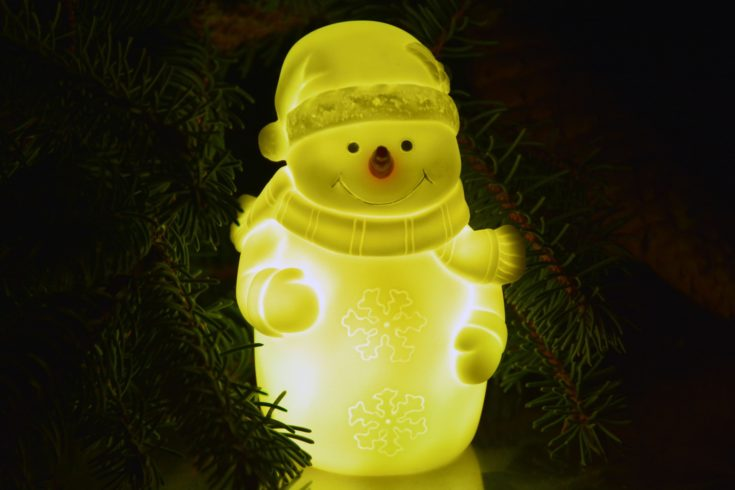 Adorable smiling snowman glowing in a semi golden light with a Christmas tree on its background