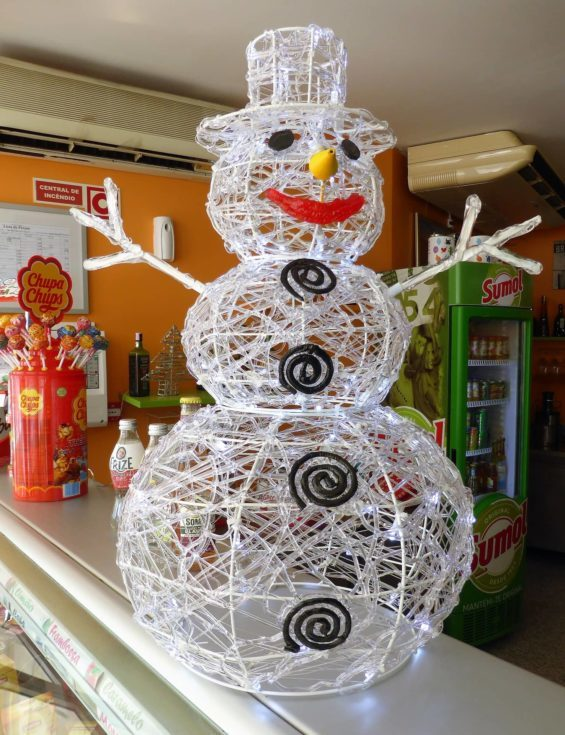 White handmade with wires and lights Snowman standing on a store stall with lollipops on its background