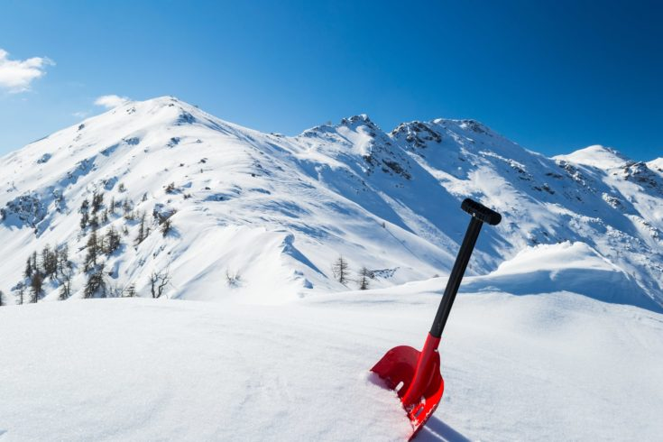 Red avalanche shovel in powder fresh snow. Scenic snowcapped high mountain background. Winter season in the italian Alps.