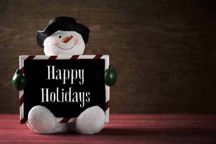 a funny snowman holding a black signboard with the text happy holidays written in it against a rustic wooden surface with a negative space on the right