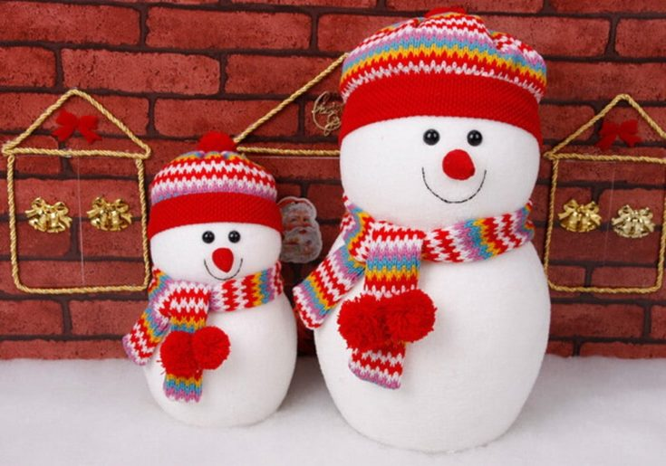Two snowman standing on a snow wearing colorful and pleasing to the eye hats and scarf with brick wall on the background