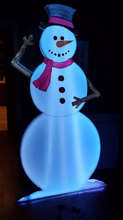 LED smiling Snowman glowing in light standing on a solid platform