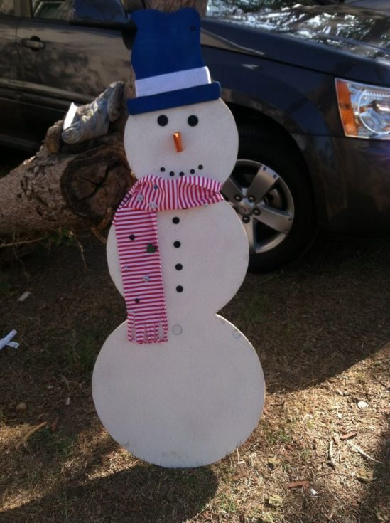 DIY Wooden snowman standing on the ground with a log of tree on its back and a car on its background