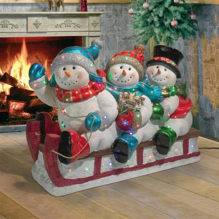 Three snowman riding on a sleigh indoor with fireplace on the background