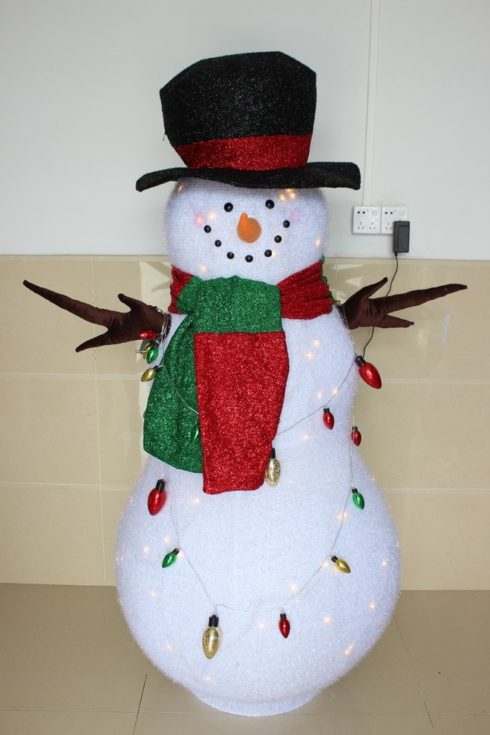 Indoor DIY snowman adorned with hat, scarf and draped in colorful lights around its body