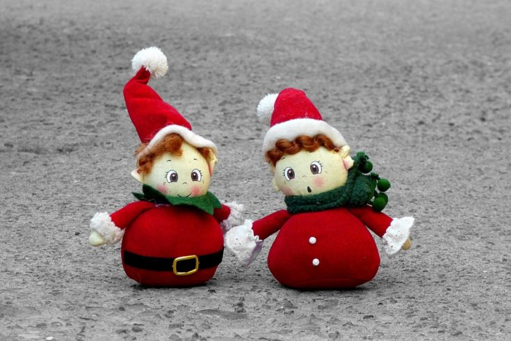 Two cute little santa dressed snowman standing on a solid pavement