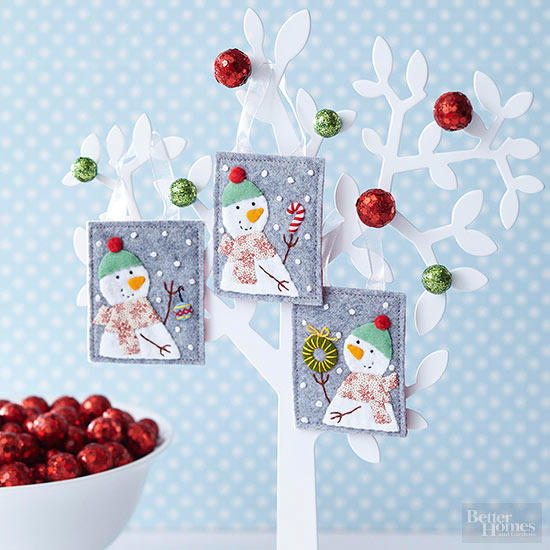 Three cute snowman craft hanged on a white treelike design with green and red balls attached on it as well