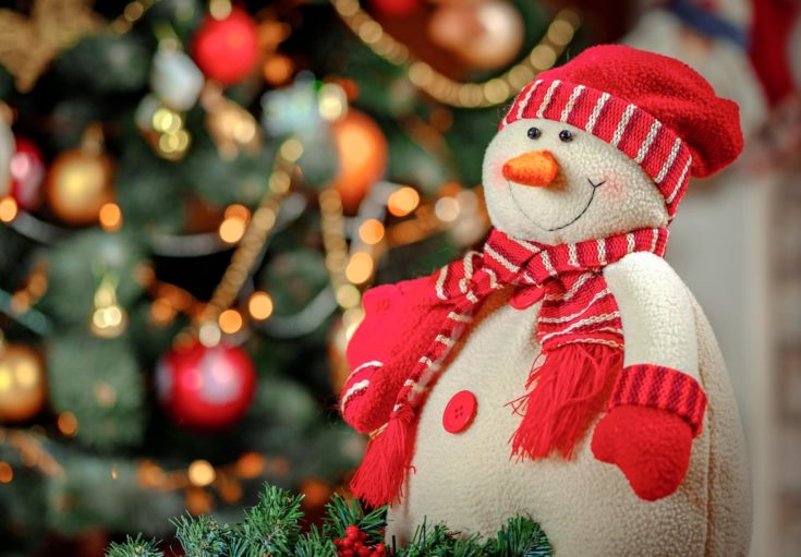 Snowman made of cloth adorned with red hat, scarf and gloves with a blurred christmas tree with decorations on the background