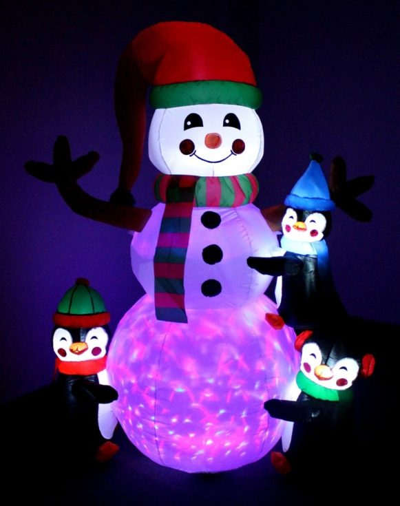 Smiling snowman glowing with lights wearing santa hat with three little plastic penguins hugging it