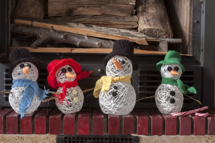 a horizontal frontal view of a decorated fireplace with snowmen