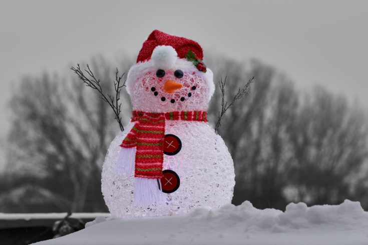 Handmade smiling snowman adorned with red clothings standing on a snow outside with blurred trees on the background