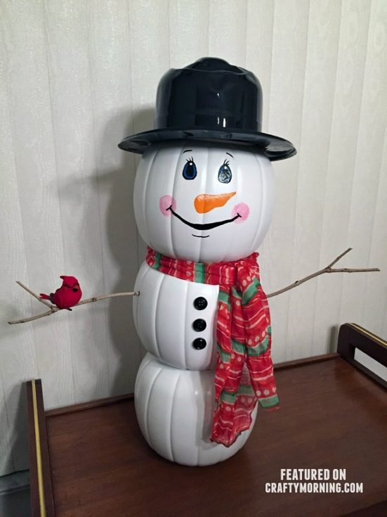 Pumpkins painted with white placed on top of each other to form a snowman figure then adorned with hat and scarf and wooden arm with a drawn eyes, nose and smile
