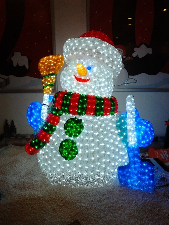 Christmas themed Snowman placed outside glowing in white, red, green, orange and blue lights