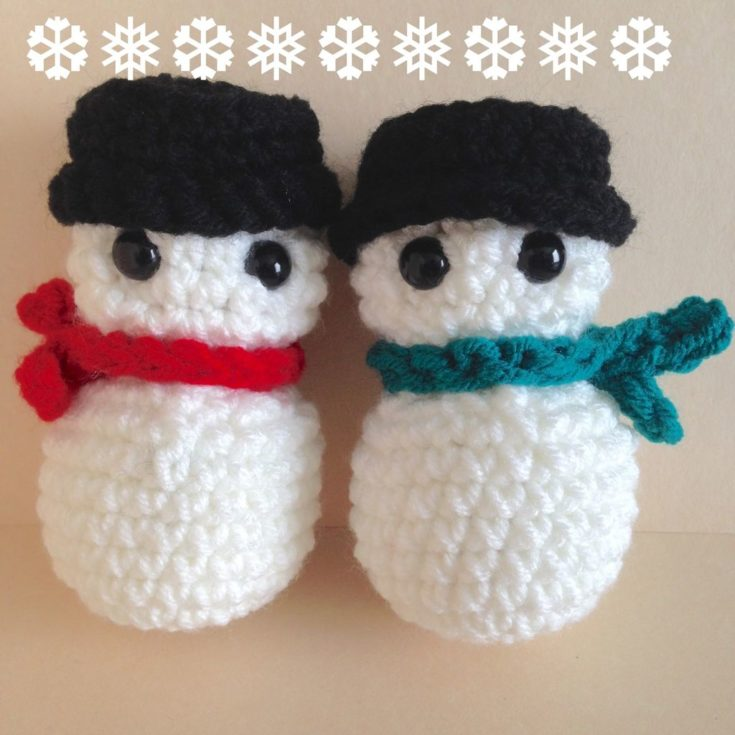 Two fluffy snowman adorned with hat and scarf with a bulgy black eyes attached