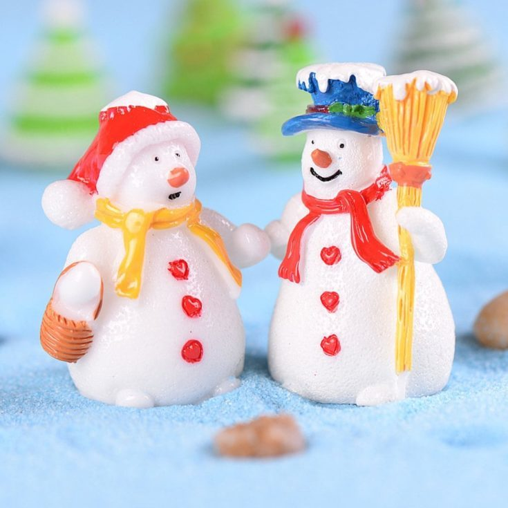 Miniature clay like snowman couple both wearing a hat and heart shaped buttons on their body standing on a light blue sand