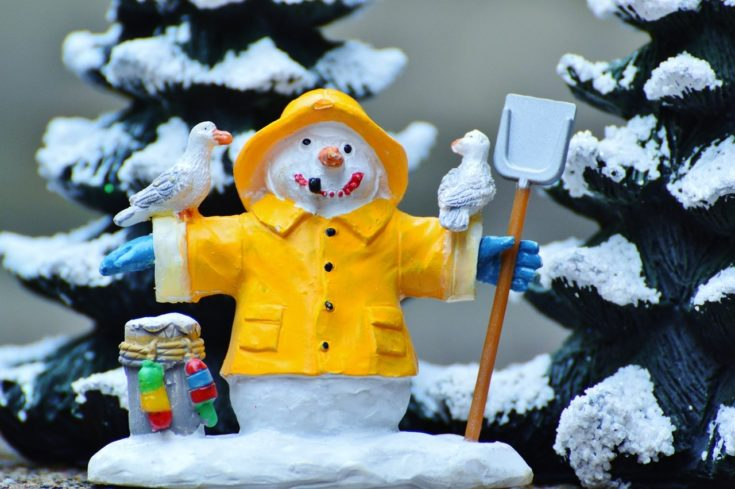 Miniature handmade Snowman wearing yellow coat spreading its arms wide having two birds resting in it and holding a shovel in its hands