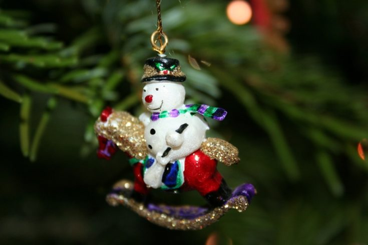 Christmas tree decoration snowman riding a little red horse glowing in glitters