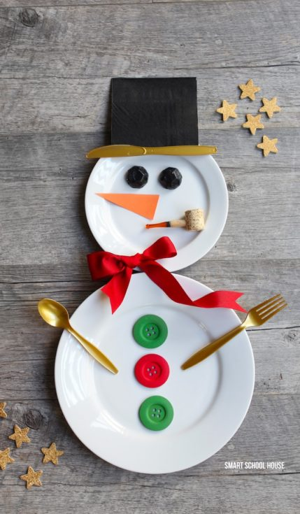 Two plates decorated with ribbon and buttons to look like a snowman using spoon and fork as its arms and knife as part of the hat
