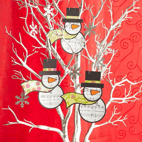 Snowman with musical symbols printed in its body and head hanging on the twigs of the indoor tree