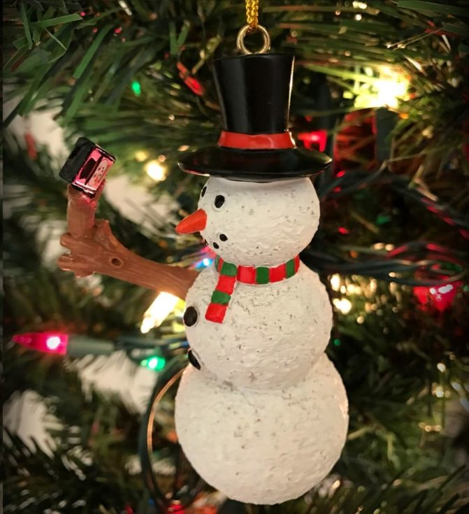 Christmas tree snowman decoration with a handmade wooden arm holding a miniature camera taking a selfie