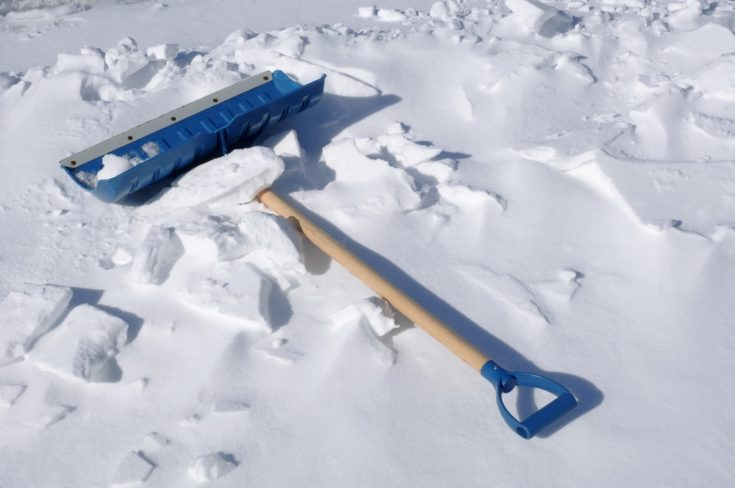 Blue snow shovel on the pearly white snow