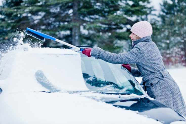 Woman Removing Snow from a Car with a Broom after the Blizzard