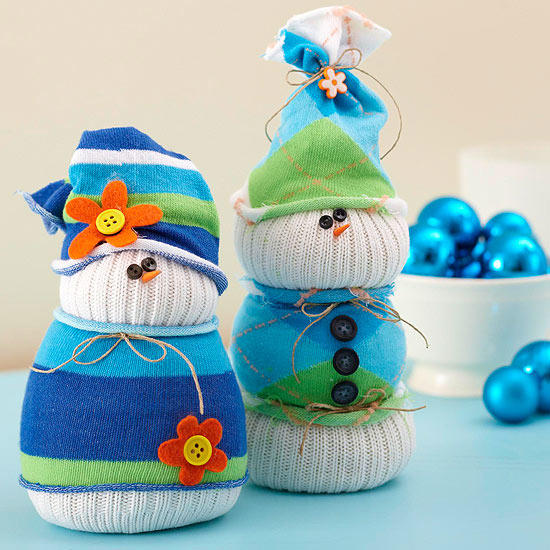 Snowman inspired made out of socks adorned with blue clothings and hat with buttons attached on its body and eyes as well