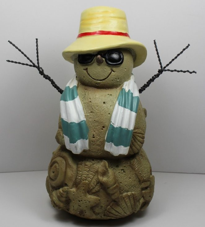 Stonemade snowman with several carved clams and shells on its bottom decorated with glasses, hat and a scarf attached with a wire twisted to form as an arm
