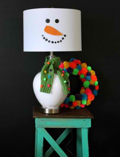 A lamp shade with snowman inspired head standing on a small table with colorful pompom on its side