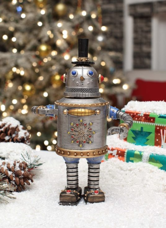 Snowman inspired made of tin can with snowflake design on its belly and wearing a little black hat standing on a snow