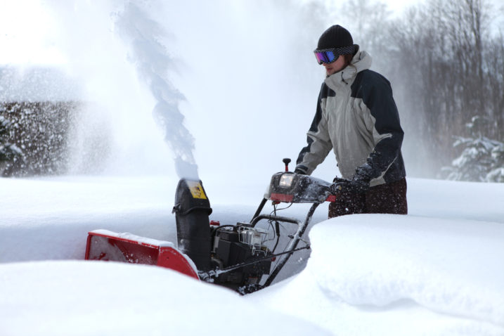 Man pushing snowblower forward with a snow waist deep