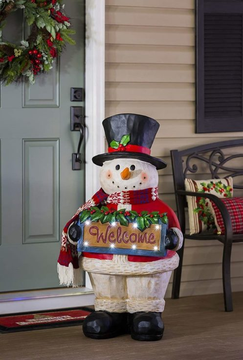 Snowman wearing Santa inspired coat and black hat holding the welcome sign in front of a door and a bench