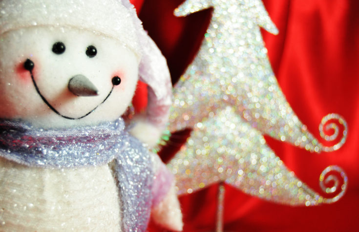 Close up snowman shining in glitters with blurred tree like material on the background