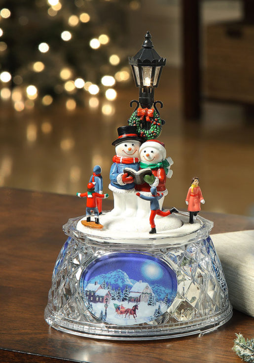 Miniature snowman couple holding a book under a street light surrounded by four little human all placed in a rounded crystal like glass
