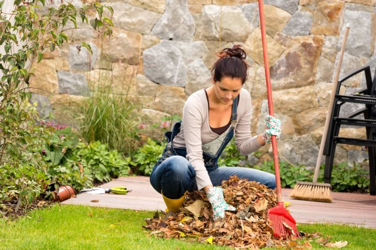 Young woman raking leaves autumn pile garden veranda housework sweeping
