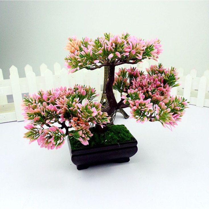 Pink flowering Indoor bonsai tree with white fence on the background and a miniature eiffel tower