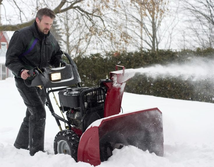 man using snow blower during winter storm