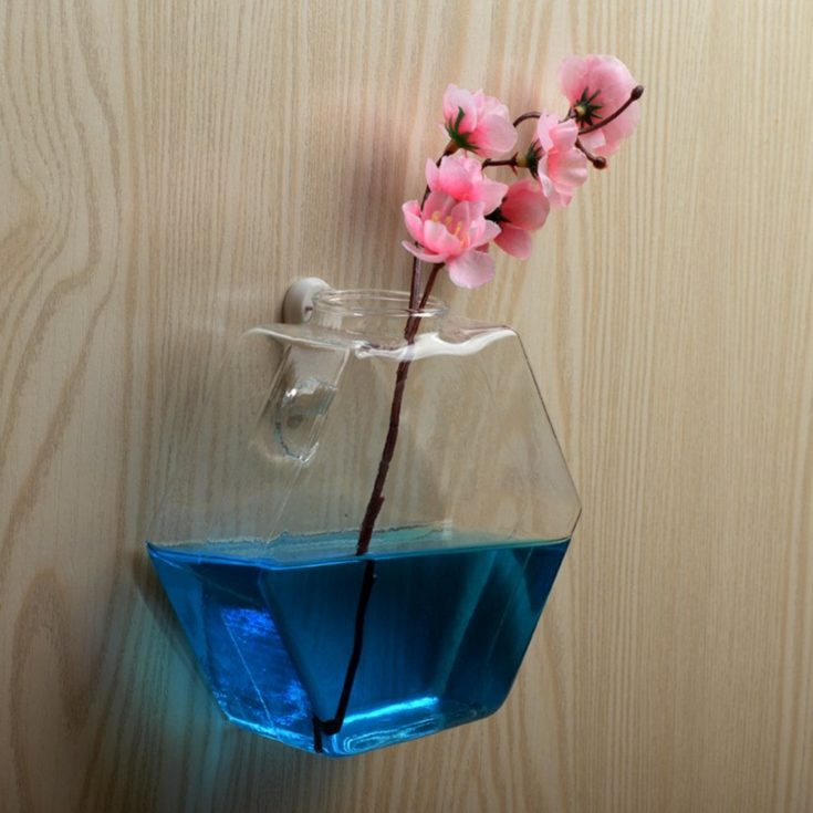 Transparent glass terrarium half filled with blue water with the stem of a pink flower submerged