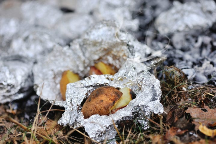 Baked potatoes covered with aluminum foil roasting in a bonfire