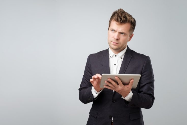 Examining new gadget. Confident young handsome man in suit working on digital tablet while standing against white background. Try to understand how to use new features