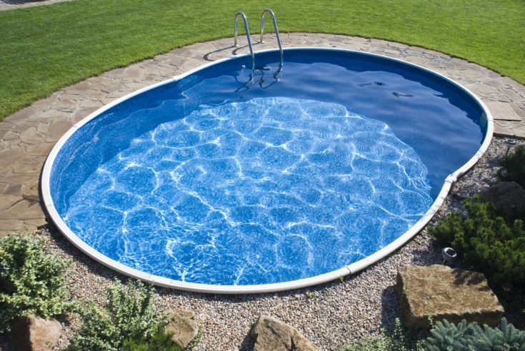 Small irregular circle shaped pool surrounded with Bermuda grass