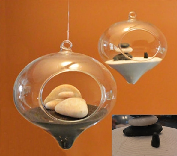 Hanging Round glass with sand inside and several white and black stones.