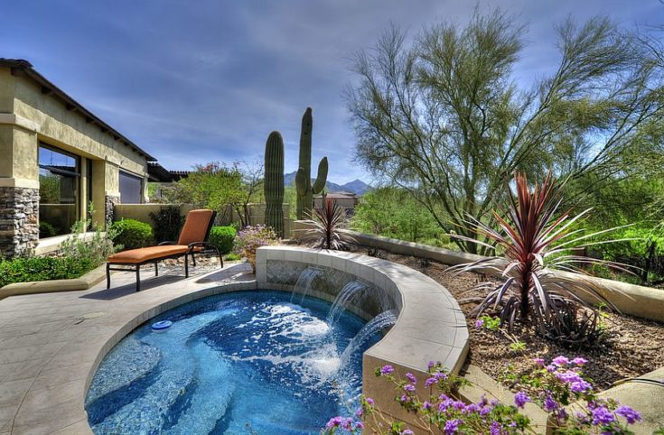 Elegant swimming pool with fountain on it's side situated in a peaceful and refreshing backyard
