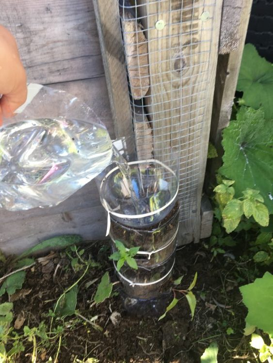 Water poured on the top plastic bottle,this serve as a water container for the tower garden.