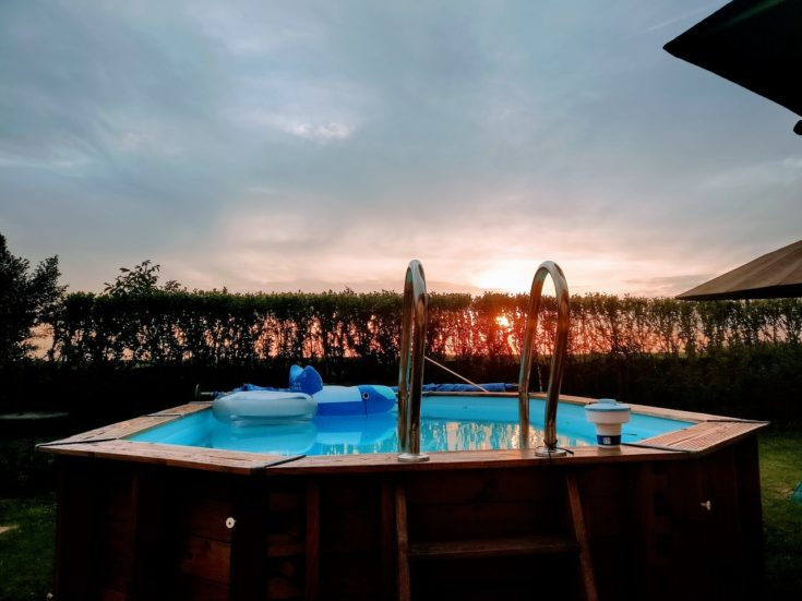DIY Wooden backyard swimming pool with two inflatable toys in a sunset